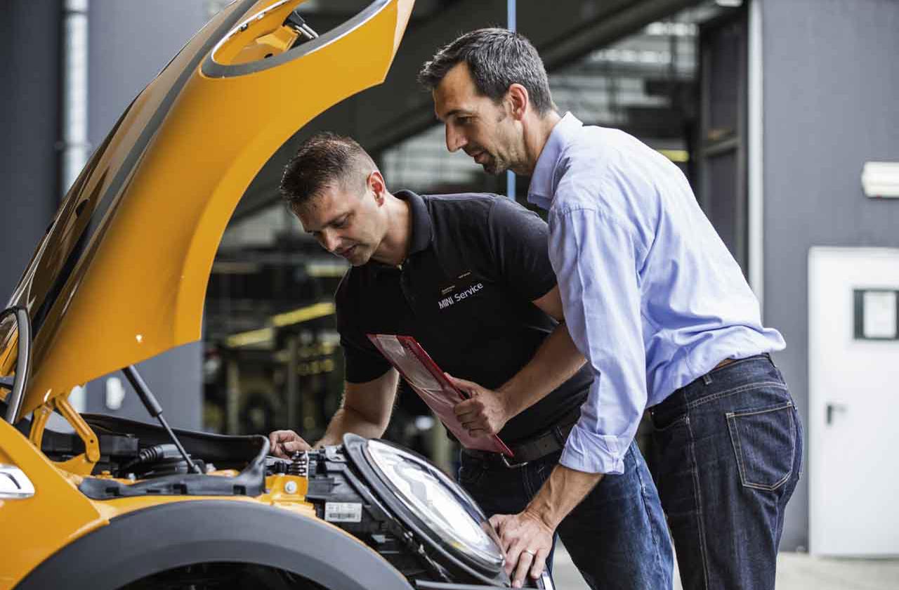 Mechaniker schaut über das MINI Abo eines Kunden in der Nähe.